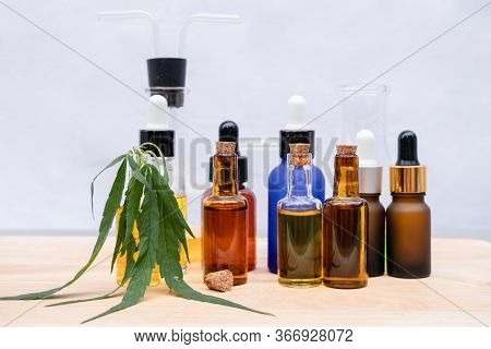 Glass Bottle With Extracting Cbd Oil Formula And Hemp Leaf On A Wooden Floor. Medical Cannabis Conce