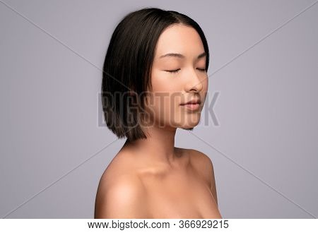Calm Asian Woman With Closed Eyes Resting After Skin Care Procedure Against Gray Background