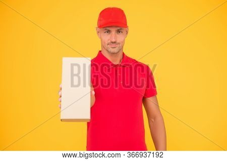 Your Package In Our Safe Hands. Package Boy In Red Uniform Yellow Background. Delivery Man Hold Box