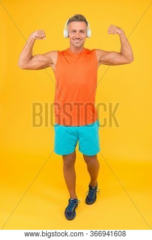 Music Is Power. Happy Man Fix Arms Yellow Background. Fit Guy Show Muscle Power. Gym Clothes And Spo