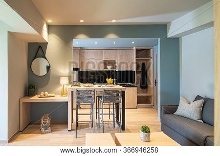 Modern Grey And Wooden Interior Of Small Studio Apartment. Front View Of Hotel Flat Room Witn Kitche