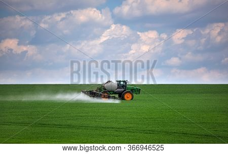 Tractor Spraying Green Wheat Field. Agricultural Work