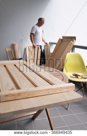 Grey-haired Handyman In Home Clothes Choosing Wooden Part. One Wooden Shelf Laying On Round Table. H