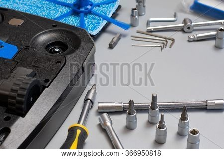 Robot Vacuum Cleaner. Copy Space. Vacuum Cleaner Robot Repair On Grey Background With Tools. Vacuum