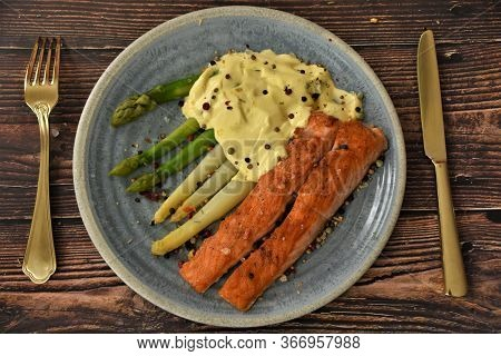 Fried Sturgeon Fish With Boiled Asparagus In Sauce, A Golden Fork With A Knife On A Wooden Table