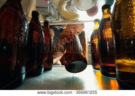 Caucasian Woman Takes Cold Refreshing Beer From Out The Fridge, Inside View From Fridge Of Hand Hold