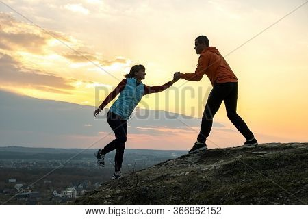 Man And Woman Hikers Helping Each Other To Climb Stone At Sunset In Mountains. Couple Climbing On Hi
