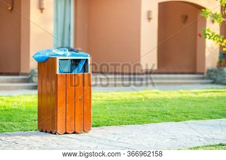 Yellow Wooden Trash Can Outdoors On The Side Of Sidewalk In Park. Garbage Container On Street Outsid