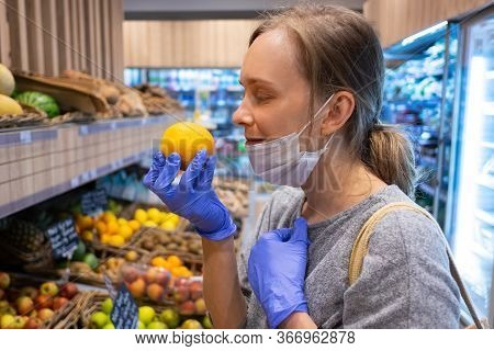 Delighted Woman Taking Off Face Mask For Smelling Lemon, Choosing Fruits In Grocery Store. Customer
