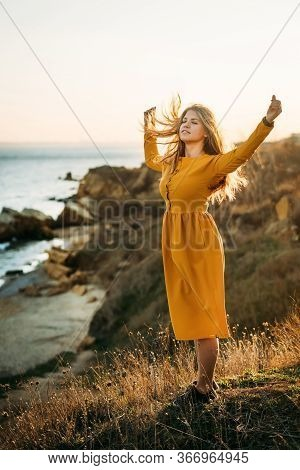 Calm Young Woman Stands On The Edge Of A Cliff In A Yellow Dress With Her Hands Up And Enjoys Wind A