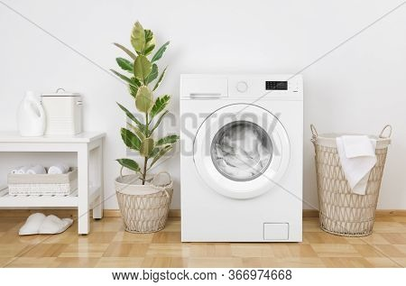 Laundry Room Interior With Washing Machine, Basket And White Wall