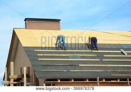Asphalt Roofing Shingles. Building Contractors Laying Bitumen Waterproofing Membrane Berofe Laying A