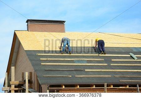 Asphalt Roofing Shingles. Building Contractors Laying Bitumen Waterproofing Membrane Berofe Laying A