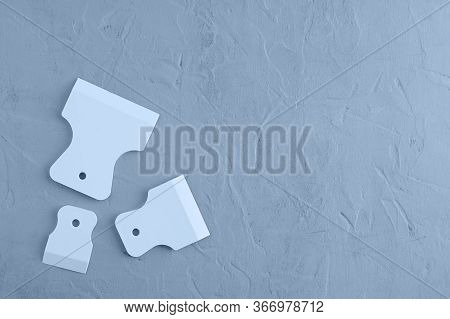 Three Rubber Spatulas For Grouting Tiles On A Gray Concrete Background. View From Above.