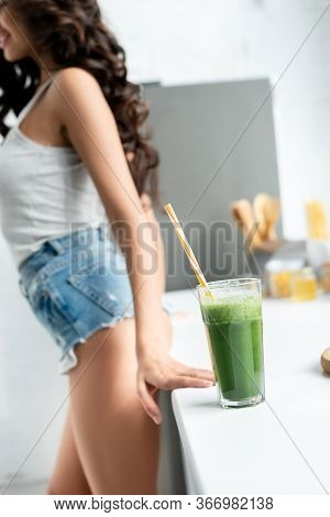 Selective Focus Of Glass Of Smoothie On Worktop And Sexy Woman In Kitchen