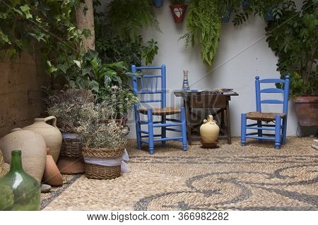 Beautiful Andalusian patio with plants, blue chairs, wooden table and vases placed on a mosaic stone floor. Crdoba, Andalusia, Spain. Travels and tourism.