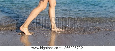 Close-up Young Adult Beautiful Slim Female Barefoot Leg Girl Walking Along Clear Water Waves Of Sea