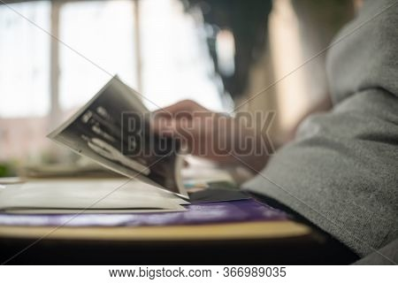 Young Woman Holds An Old Photo Album On Her Lap And Looks At Black And White Photos, Close Up
