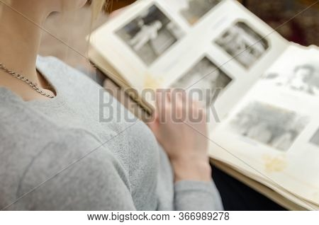 Girl In A Gray Sweatshirt Is Sitting On The Sofa And Looking At Old Black-and-white Photos In A Phot