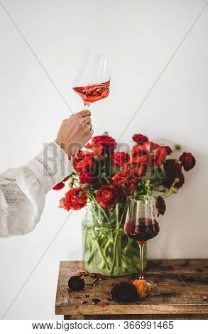 Womans Hand With Rose Wine In Glass And Red Flowers
