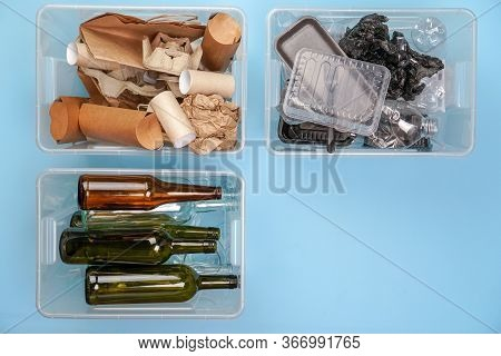 Sorting Garbage. Three Transparent Containers With Trash On A Blue Background: Glass, Plastic, Paper