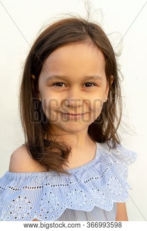 Portrait Of A Girl Of 7 Years Old With Brown Hair And Brown Eyes In A Gentle Blue Romantic Blouse On