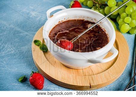 Sweet Fruity Chocolate Fondue Dessert With Strawberry, Grape And Kiwi, Light Blue Concrete Backgroun
