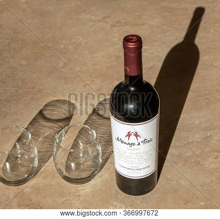 Bemidji, Mn - 15 May 2020: Bottle Of Uncorked Red Wine On A Table Top Alongside Two Stemless Wine Gl