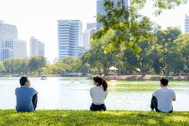 Asian Young Three Man And Woman Talking And Relaxing With They Friend And Wearing Mask Sitting Dista