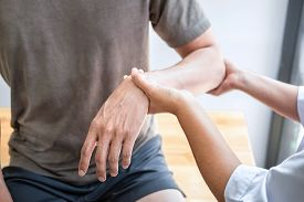 Female Physiotherapist Working Examining Treating Injured Arm Of Athlete Male Patient, Stretching An