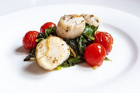 Pan Seared Scallops With Ginger And Black Pepper Served On A Bed Of Green Swiss Chard And Decorated