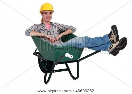 Construction worker sitting in a wheelbarrow