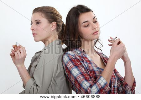 Girl lighting a cigarette as another snaps one in half