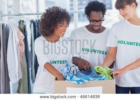 Cheerful volunteers taking out clothes from a donation box in their office