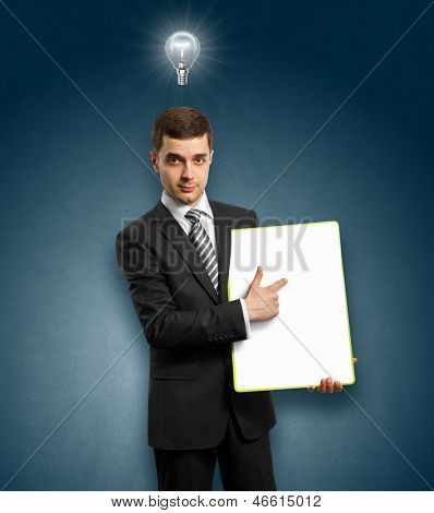 Idea concept. Businessman holding empty write board in his hands, with lamp above his head