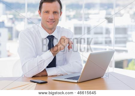 Smiling businessman leaning on his desk in his office
