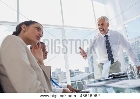 Furious boss yelling at colleagues during a meeting