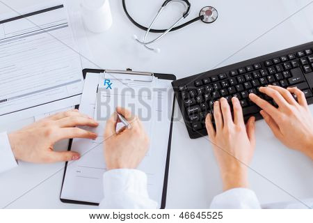 picture of doctor and nurse writing prescription paper
