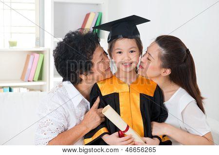 Kindergarten graduation. Asian family, grandparent and parent kissing grandchild on her kinder graduate day.