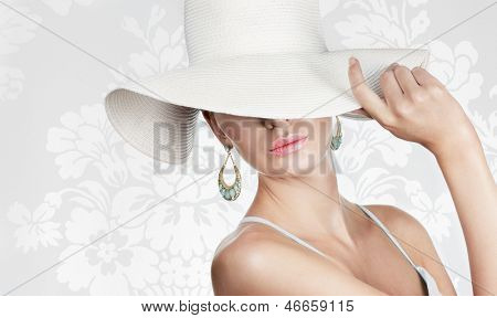 Elegant woman in white hat on white fancy background. Space for text.