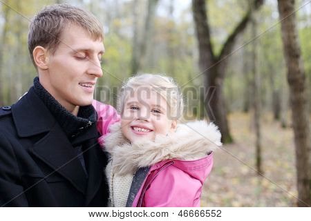 Happy father and daughter in autumn forest. Shallow depth of field.
