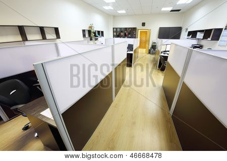 Corridor with wooden floor and empty working areas with desktops in office.