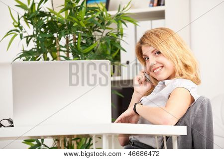 smiling woman sitting, speaking on phone and looking at her watch in the office