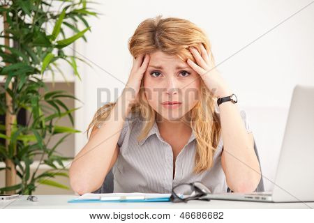 tired young woman on the laptop having some problems in the office