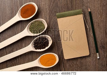 notebook and pencil for recipes and spices in spoons on wooden table