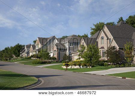 Houses On Upscale Suburban Street In Morning Sunlight