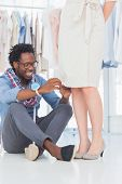 Attractive fashion designer sitting and fixing needles on dress poster