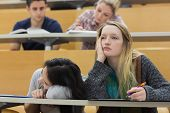 Demotivated students sitting in a lecture hall with one girl napping in college poster