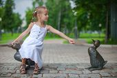 Little girl feeding the ducks figure in the park poster