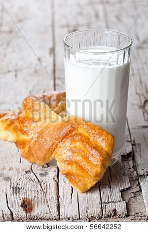 glass of milk and two fresh baked buns on rustic wooden table